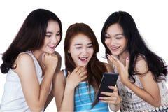 Группа в составе девушки читая сообщение на мобильном телефоне Стоковые Изображения RF