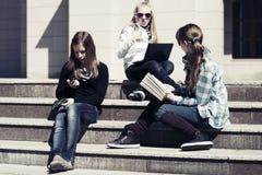 Группа в составе девушки школы сидя на шагах в кампус Стоковые Фотографии RF