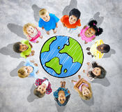 Группа в составе дети вокруг глобуса в серой предпосылке стоковые изображения