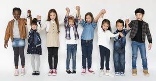 Группа в составе дети держа счастье выражения стороны рук усмехаясь дальше стоковое изображение
