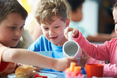 Группа в составе дети есть обед в школьном кафетерии Стоковые Фотографии RF