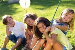 Группа в составе дети имея потеху в парке Стоковые Изображения