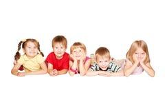 Группа в составе дети имея потеху, лежа на поле Стоковые Фото
