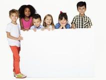 Группа в составе дети показывая доску Copyspace Стоковая Фотография