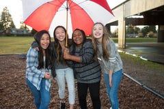 Группа в составе дети под зонтиком в дожде Стоковая Фотография