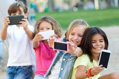Группа в составе дети принимая selfie в парке Стоковые Изображения RF
