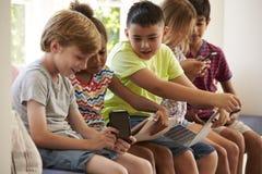 Группа в составе дети сидит на сиденье у окна и использует технологию стоковые фото