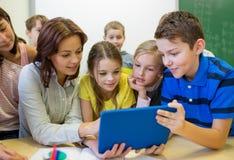 Группа в составе дети с ПК учителя и таблетки на школе Стоковые Изображения RF