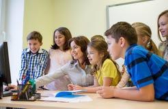 Группа в составе дети с учителем и компьютером на школе Стоковые Изображения