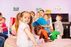 Группа в составе дети слушает к книге чтения учителя Стоковое Изображение