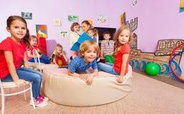 Группа в составе дети слушает к учителю читая книгу Стоковое Фото