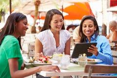 Группа в составе женские друзья наслаждаясь обедом в внешнем ресторане стоковые фото