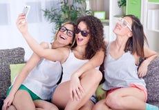Группа в составе 3 женских друз имея потеху с smartphones Стоковая Фотография RF