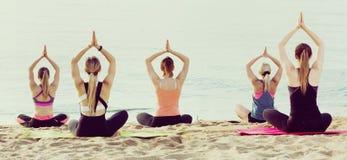 Группа в составе женщины выполняя йогу на пляже Стоковая Фотография