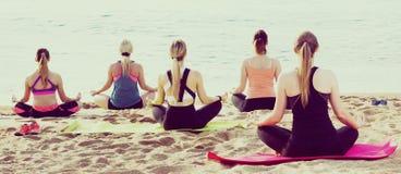 Группа в составе женщины выполняя йогу на пляже Стоковое Изображение