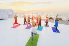 Группа в составе женщины делая йогу на восходе солнца около моря Стоковые Фотографии RF