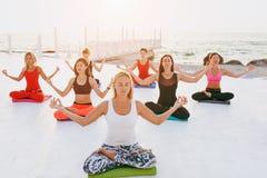 Группа в составе женщины делая йогу на восходе солнца около моря Стоковое фото RF