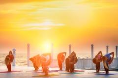 Группа в составе женщины делая йогу на восходе солнца около моря Стоковая Фотография RF