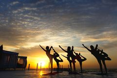 Группа в составе женщины делая йогу на восходе солнца около моря Стоковая Фотография