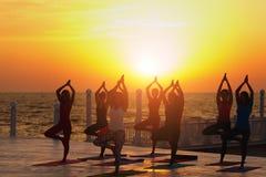 Группа в составе женщины делая йогу на восходе солнца около моря Стоковое Изображение RF
