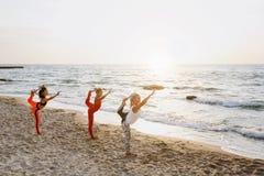 Группа в составе женщины делая йогу на восходе солнца около моря Стоковые Изображения