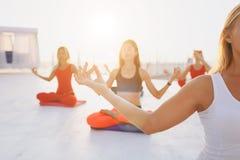 Группа в составе женщины делая йогу на восходе солнца около моря Стоковое Изображение