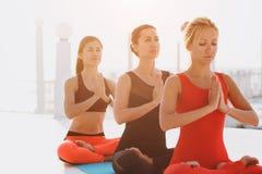 Группа в составе женщины делая йогу на восходе солнца около моря Стоковые Изображения RF