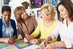 Группа в составе женщины делая лоскутное одеяло совместно Стоковые Фото