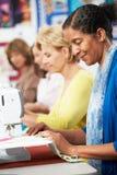 Группа в составе женщины используя электрические швейные машины в классе Стоковая Фотография RF