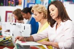 Группа в составе женщины используя электрические швейные машины в классе Стоковая Фотография