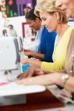 Группа в составе женщины используя электрические швейные машины в классе Стоковое Изображение RF