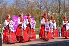 Группа в составе женщины в национальных костюмах танцует русские танцы Стоковые Фотографии RF