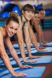 Группа в составе женщины на спортзале нажимает вверх тренировку разминки Стоковое Фото