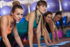 Группа в составе женщины на спортзале нажимает вверх тренировку разминки Стоковое фото RF