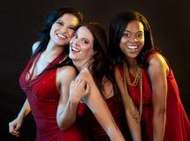 Группа в составе женщины нося платья красного цвета Стоковое Фото