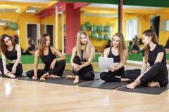 Группа в составе женщины обсуждая план с личным тренером в спортзале Стоковое Изображение