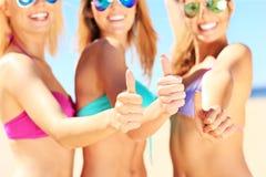 Группа в составе женщины показывая одобренные знаки на пляже Стоковые Фото
