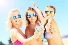 Группа в составе женщины показывая одобренные знаки на пляже Стоковые Фотографии RF