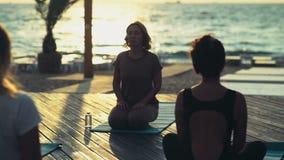 Группа в составе женщины практикуя йогу на замедленном движении пляжа акции видеоматериалы