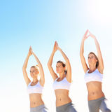 Группа в составе женщины практикуя йогу на пляже Стоковая Фотография RF