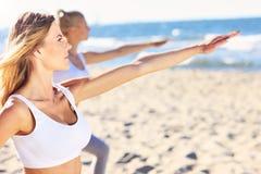 Группа в составе женщины практикуя йогу на пляже Стоковая Фотография