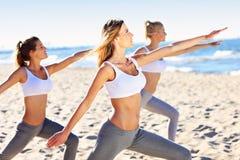 Группа в составе женщины практикуя йогу на пляже Стоковое Изображение