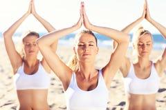 Группа в составе женщины практикуя йогу на пляже Стоковые Изображения RF