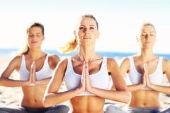 Группа в составе женщины практикуя йогу на пляже Стоковое Изображение RF