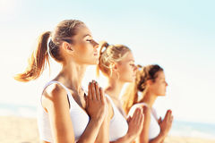 Группа в составе женщины практикуя йогу на пляже Стоковые Фотографии RF