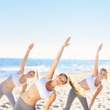 Группа в составе женщины практикуя йогу на пляже Стоковые Изображения