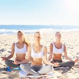 Группа в составе женщины практикуя йогу на пляже Стоковое фото RF