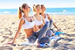 Группа в составе женщины практикуя йогу на пляже Стоковые Фото