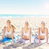 Группа в составе женщины практикуя йогу на пляже Стоковое Фото