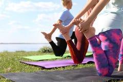 Группа в составе женщины практикуя йогу около реки Стоковые Изображения RF